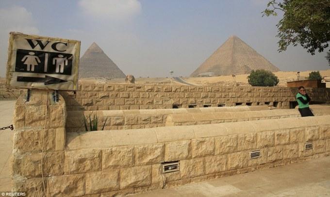 """<p class=""""Normal""""> Một phụ nữ đang đứng chờ vào nhà vệ sinh đối diện tượng Nhân sư gần khu vực kim tự tháp Giza, ngoại ô Cairo, Ai Cập.</p>"""