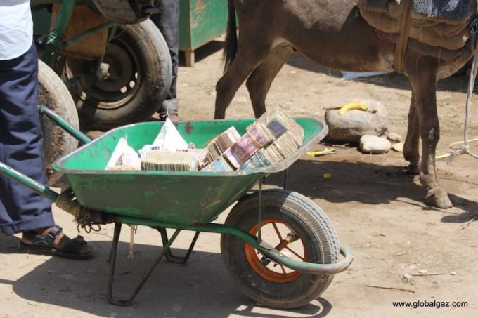 <p> Người dân chất tiền trên những chuyến xe cút kít và rao bán như một mặt hàng rau hay hoa quả.</p>