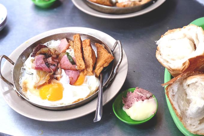 """<p class=""""Normal""""> Quán có nhiều nhân bánh khác nhau song được yêu thích nhất là nhân thịt nguội và ốp la. Phần ốp la gồm ổ bánh mì dài khoảng một gang tay, ăn cùng chảo thức ăn nóng hổi, đầy ắp. Thành phần trong chảo gồm hai trứng gà chiên, hành tây, jambon, chả lụa, chả quế, thịt ba rọi muối, xúc xích… Một phần bánh mì thập cẩm có giá khoảng 50.000 đồng, phần bánh mì thịt nguội hoặc omelette giá trên 40.000 đồng.</p> <p class=""""Normal""""> Ngoài ra, bạn cũng có thể chọn phần thịt nguội thập cẩm với dăm bông, sốt, patê, ăn kèm đồ chua và bánh mì. Phần ăn này có giá mềm hơn và đều là đồ chín, dễ thưởng thức.</p>"""