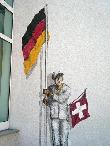 Bức ảnh người đàn ông cầm cờ của hai nước nhằm nói đến vị trí địa lý thú vị của thị trấn. Ảnh: BBC.