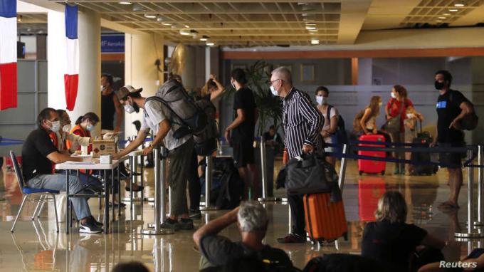 Những du khách Pháp mắc kẹt tại Bali làm thủ tục tại sân bay quốc tế Ngurah Rai, trước khi lên chuyến bay charter về nước vào ngày 28/3. Ảnh:Reuters.