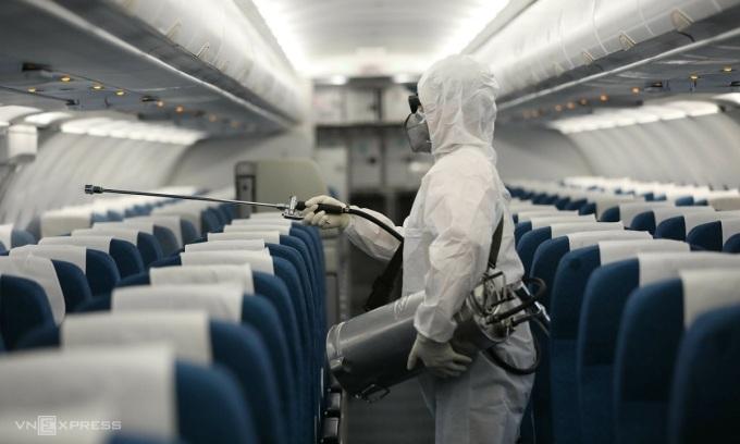 Một nhân viên y tế khử trùng máy bay của Vietnam Airlines vào ngày 4/2/2020. Toàn bộ nhân viên mặt đất và tiếp viên hàng không của hãng đều sử dụng khẩu trang và găng tay trong suốt quá trình phục vụ, tránh bị lây nhiễm chéo. Ảnh: Ngọc Thành.