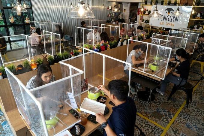 Thực khách dùng bữa trưa trong nhà hàng lẩu tại Bangkok, Thái Lan, ngày 8/5. Các nhà hàng có sử dụng vách ngăn nhựa hoặc kính để giữ khoảng cách an toàn. Ảnh: Athit Perawongmetha/Reuters.