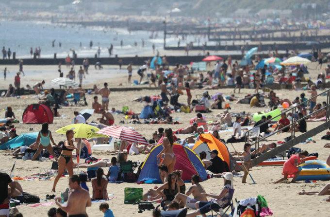 Hàng ngàn người bỏ ô tô ven đường để đổ xô đến bãi biển Bournemouth ở Dorset. Ảnh: PA.