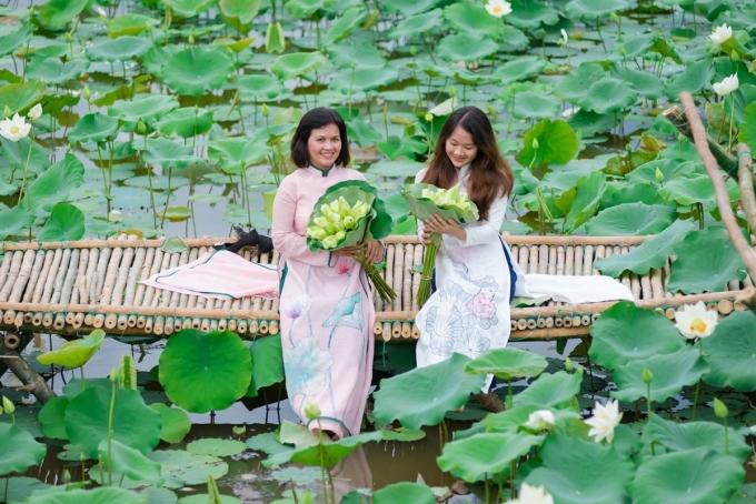 Nhiều chị em diện áo dài chụp cùng hoa sen trắng ở làng cổ Phước Tích bên bờ sông Ô Lâu.