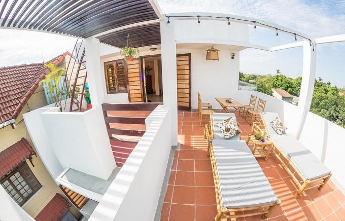 Sân thượng bài trí giường tắm nắng, thư giãn và bàn ghế để du khách trò chuyện, giao lưu. Các mảng tường trắng, gạch đỏ gợi cảm giác thân thiện, bình dị.