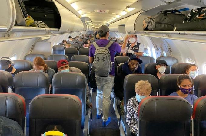Hành khách khó thực hiện giãn cách xã hội trên máy bay, do đó cần đeo khẩu trang và mang theo dung dịch khử trùng. Ảnh:Deccan Herald.