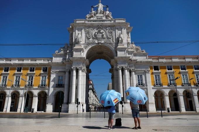 Hai hướng dãn viên đang đứng chờ du khách ở Lisbon hồi giữa tháng 7. Ảnh: Reuters.