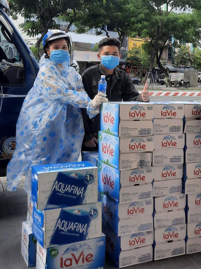 Quách Minh Duyên (trái) vận chuyển nước ủng hộ cho các bệnh viện đến địa điểm tập kết.
