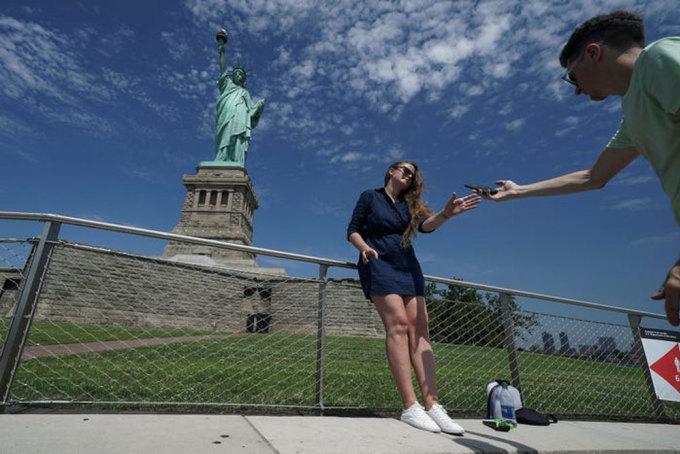 Nhiều quốc gia và các điểm tham quan nổi tiếng thế giới đang mở cửa đón khách trở lại, nhưng khung cảnh đã khác trước. Đảo Liberty cùng các điểm tham quan ngoài trời khác ở New York, Mỹ bắt đầu đón khách cuối tháng 7. Du khách được yêu cầu đeo khẩu trang, giữ khoảng cách xã hội an toàn. Trong ảnh, du khách chụp ảnh tại Tượng Nữ thần Tự do vào 20/7. Ảnh: Carlo Allegri/Reuters