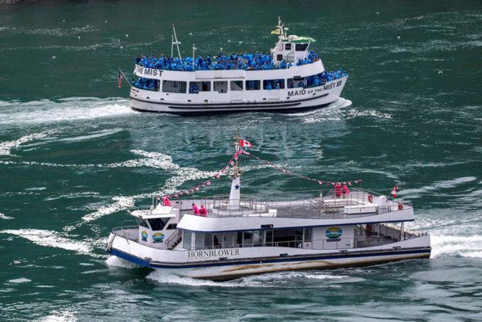 Du thuyền Mỹ Maid Of The Mist (trái) bên cạnh đồng nghiệp mang quốc tịch Canada, tàu Hornblower ở thác Niagara ngày 21/7. Bức ảnh khiến nhiều người chú ý khi phản ánh tình hình các quốc gia đang đối phó với đại dịch khác nhau như thế nào. Trong khi thuyền Mỹ chật cứng, thì thuyền Canada chỉ có vài khách. Ảnh: Carlos Osorio/Reuters