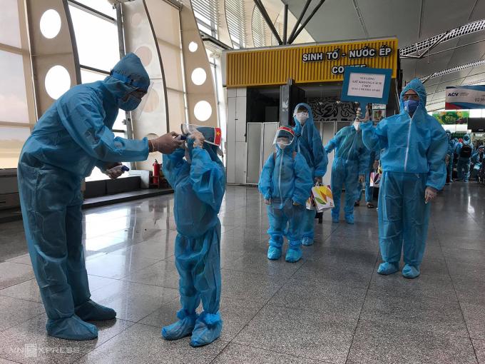 Hành khách được kiểm tra thân nhiệt trước khi lên máy bay. Ảnh: Phong Vân/VnExpress
