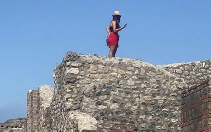 Nữ du khách trèo lên tường của nhà tắm trong thành cổ Pompeii. Ảnh: Antonio Irlando