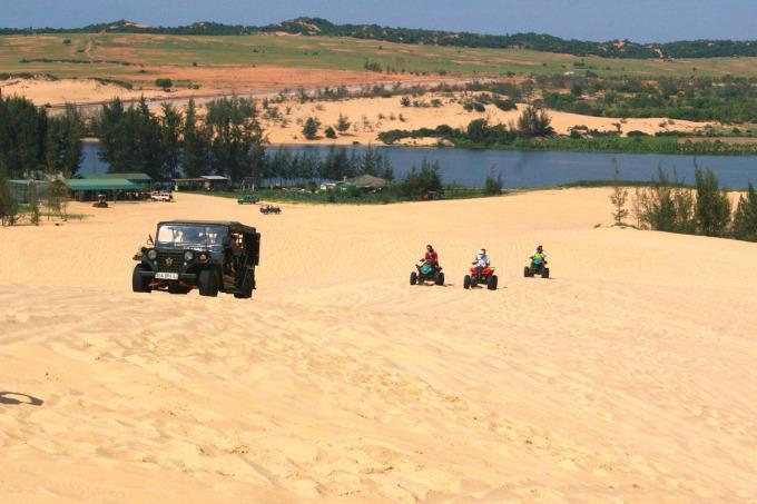Du khách tham quan và trải nghiệm dịch vụ chạy xe trên địa hình cát ở Bàu Trắng. Ảnh: Di Vỹ