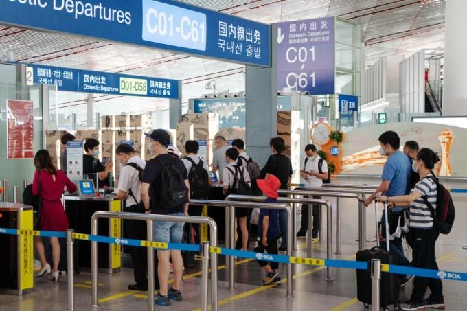 Du khách làm thủ tục chuẩn bị lên máy bay tại sân bay quốc tế thủ đô Bắc Kinh hôm 25/8. Ảnh: Bloomberg