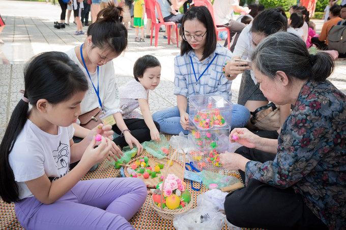 Nghệ nhân hướng dẫn du khách nhí làm con giống bột. Ảnh: Bảo tàng Dân tộc học Việt Nam.