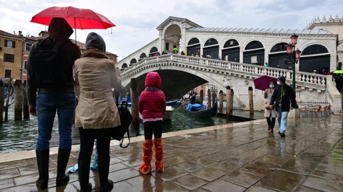 Du khách đứng đợi thủy triều ở trung tâm thành phố. Đây là một ngày lịch sử đối với Venice. Chúng tôi rất hài lòng sau hàng thập kỷ bất lực nhìn nước tràn khắp thành phố, gây ra tổn thất lớn, thị trưởng Luigi Brugnaro nói. Ảnh: AFP