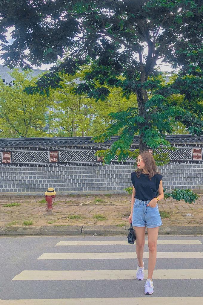 Một trong những góc chụp đẹp là tạo dáng đi sang đường, với phông nền là bức tường cùng hàng cây xanh mát đằng sau. Ảnh: Mến Bùi