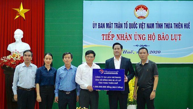 Đại diện công ty trao vật phẩm và tiền ủng hộ người dân vùng lũ.