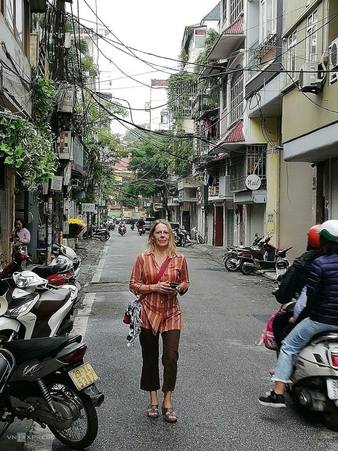 Vỉa hè không còn chỗ do xe máy lấn chiếm nên một nữ du khách phải đi bộ dưới lòng đường. Ảnh: Đăng Tú