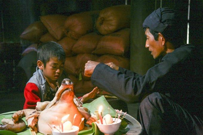Thầy mo đang làm lễ cho người cháu đích tôn bên cạnh bát gạo cúng hồn. Ảnh: Văn Thành Chương