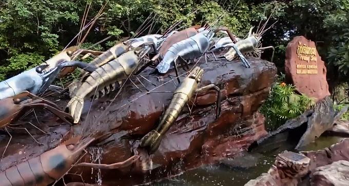 Một công trình tạo hình tảng đá với những con tôm bằng kim loại đang bò ngược dòng nước ở cổng vào của khu thác Kaeng Lamduan. Ảnh: coconuts.co