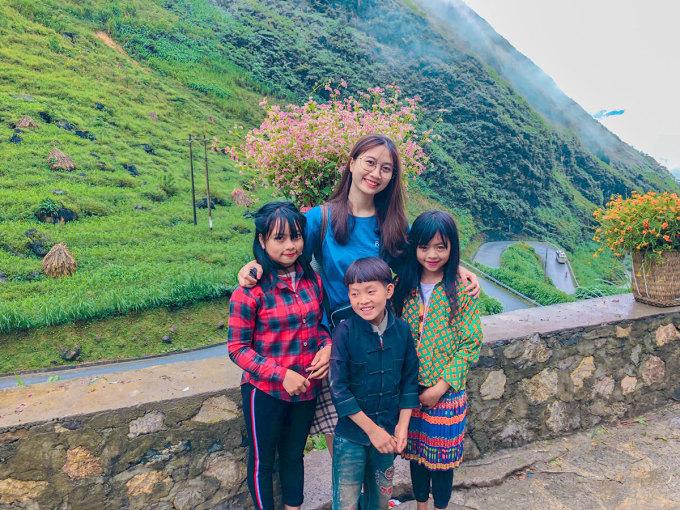 Duyên chụp ảnh cùng những em bé dân tộc đeo gùi hoa trên Dốc Thẩm Mã.