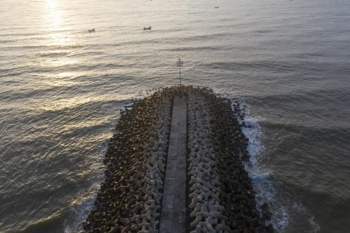 Từ cầu cảng nhìn ra hướng biển, bạn sẽ thấy hai kè chắn sóng thẳng tắp. Du khách thường thuê thuyền nhỏ hoặc thuyền thúng với giá 7.000-10.000 đồng ra kè chắn sóng chụp ảnh, đón bình minh hoặc hoàng hôn.