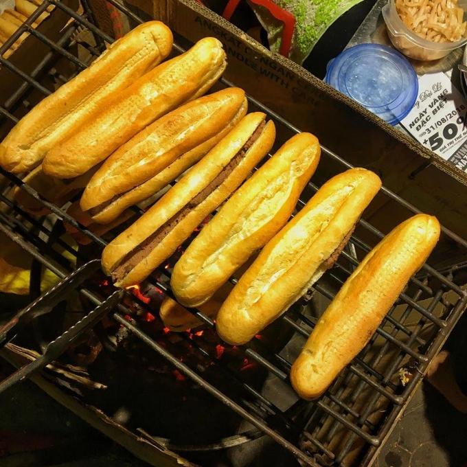 Bánh mì kẹp sẵn pate được nướng trên than trước khi rưới mỡ, thêm ruốc. Ảnh: Hoa Cỏ Dại