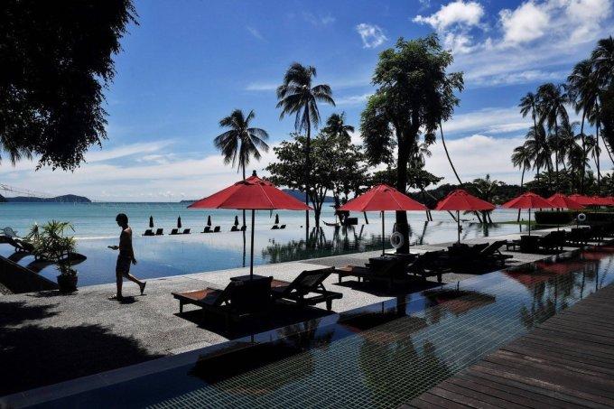 Một khách du lịch đi lại lẻ loi qua khu vực hồ bơi của khách sạn Vijitt Resort ở Phuket. Ảnh: AFP