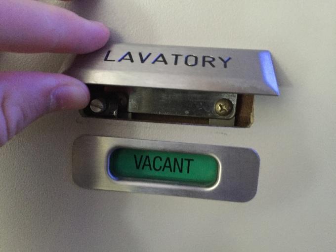 Trường hợp khẩn cấp, tiếp viên có thể mở cửa nhà vệ sinh từ bên ngoài bằng cách ấn một nút nhỏ. Nút này thường được ẩn đi sau biển báo cấm hút thuốc hoặc biển tên trên cánh cửa nhà vệ sinh. Ảnh: Travel Update