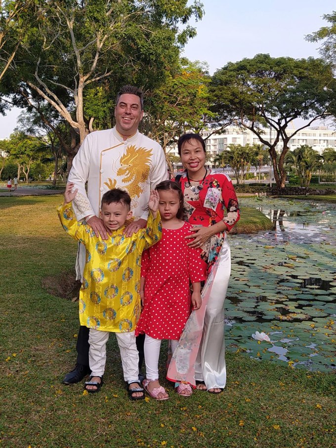 Harry Hodge (white ao dai, left) is a tourist from Canada, currently living in Ho Chi Minh City.  Married to a Vietnamese wife and two children, he often takes photos of Ao Dai with his family on Tet.  He likes to welcome the new year in Ho Chi Minh City because the streets and houses are beautifully decorated.