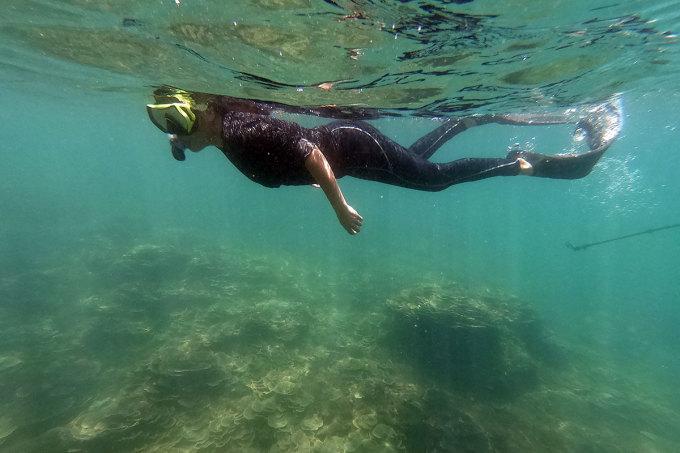 Chị Tú lặn khảo sát rạn san hô và dòng chảy trước khi cho khách xuống biển. Ảnh: Nguyễn Đông.