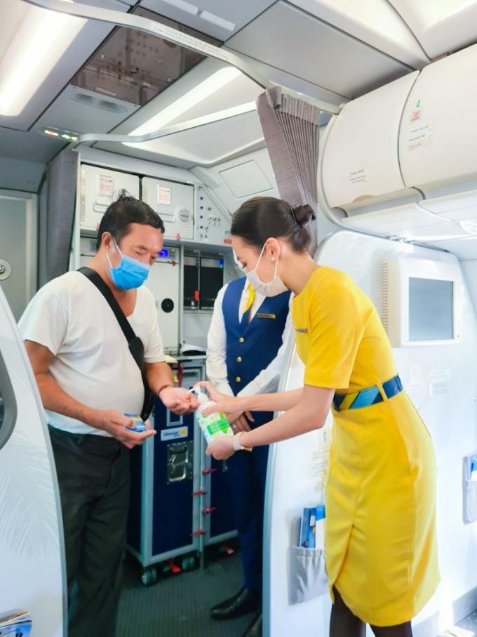Du khách được yêu cầu đo thân nhiệt, sát khuẩn tay trước khi lên tàu bay và đeo khẩu trang trong suốt hành trình.