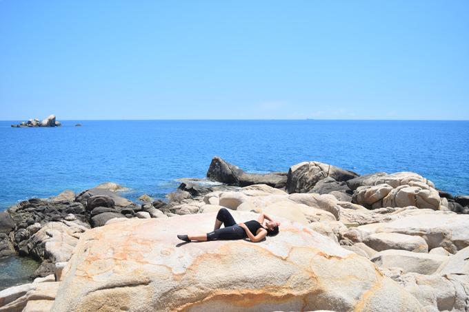 Chị Nga (phải) thư giãn một mỏm đá trên bờ biển. Sức nóng tự nhiên từ tảng đá giúp tăng tuần hoàn máu cho cơ thể.