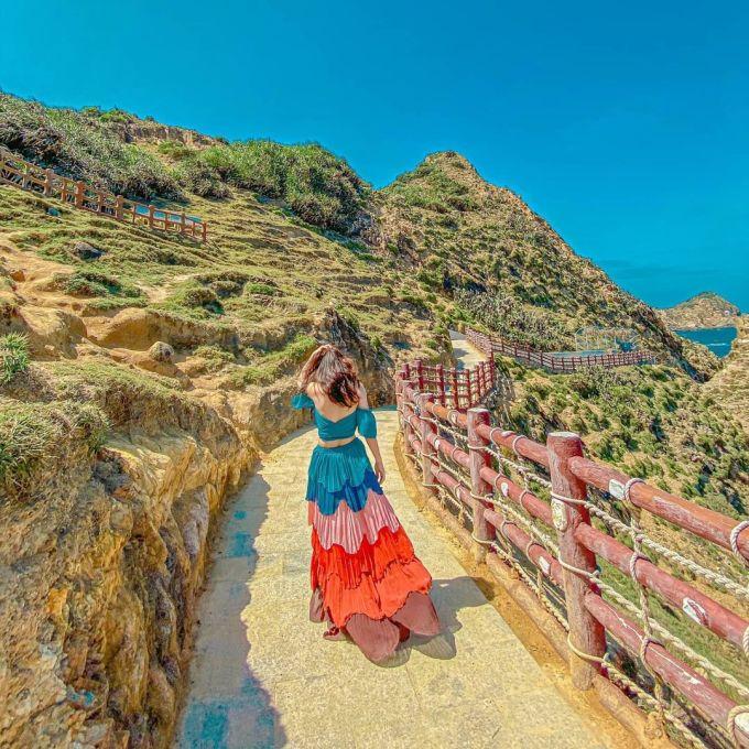 Diện những trang phục sặc sỡ, nhiều bạn nữ biến nơi đây trở thành cung đường thời trang độc đáo trên nền địa thế uốn lượn tự nhiên. Eo Gió là một eo biển nhỏ, thiên nhiên tạo nên từ những rặng núi đá cao, mỏm núi nhô ra, uốn lượn ôm lấy một vùng biển. Ảnh: Instagram/kellydiep.2212.