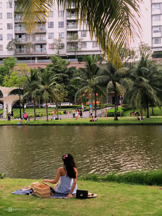 The angle chosen by many young people is to sit on the green grass next to the lake or lean against the coconut tree.  Photo: Ngan Duong