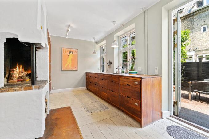 Một số phòng hợp nhất để tạo không gian rộng rãi và sáng sủa. Ví dụ, bếp và phòng gia đình ở tầng trệt, bên ngoài là vườn cây với ghế thư giãn. Ảnh: Vildmedhuse