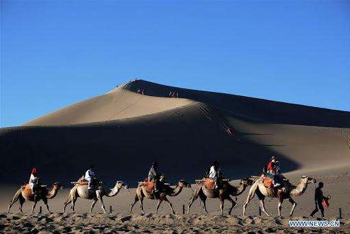 Cưỡi lạc đà là hình thức du lịch rất phổ biến, thu hút du khách tại khu thắng ảnh này núi Minh Sa và suối Nguyệt Nha. Ảnh: Xinhua