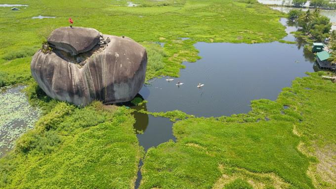 Tảng đá khổng lồ nằm giữa hồ tạo nên một khung cảnh đặc biệt thu hút du khách. Ảnh: Quốc Trung