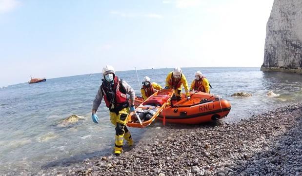 Nam du khách được đội cứu hộ đưa đi bằng cáng. Ảnh: RNLI