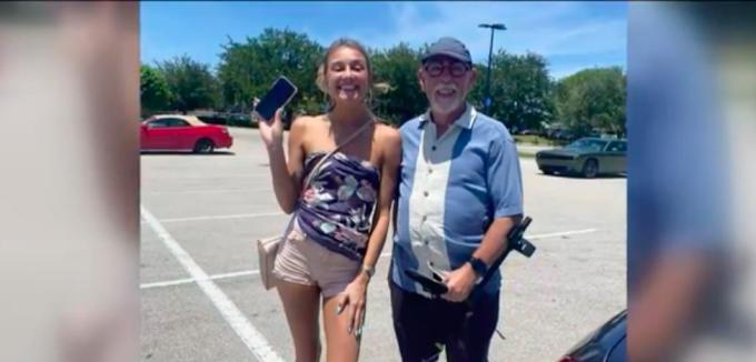 Joe Lynch (phải) trả lại điện thoại cho nữ du khách Lacy Moulton trước khi cô kết thúc kỳ nghỉ và rời khỏi Fort Myers. Ảnh: NBC