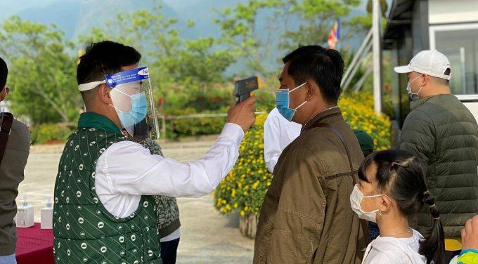 Nhân viên khu du lịch tại Fansipan trang bị khẩu trang kết hợp kính chống giọt bắn và thực hiện giữ khoảng cách với du khách. Ảnh: SW