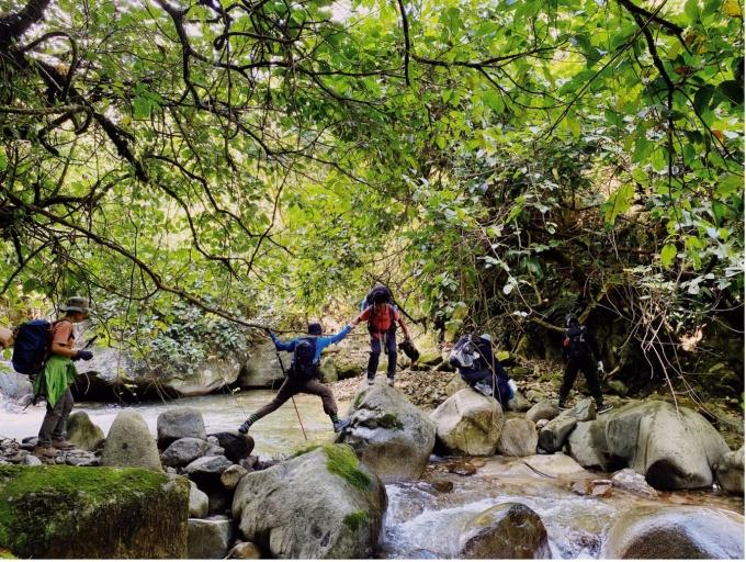 Người dẫn đường giúp các du khách vượt suối. Ảnh: Hoàng Bắc