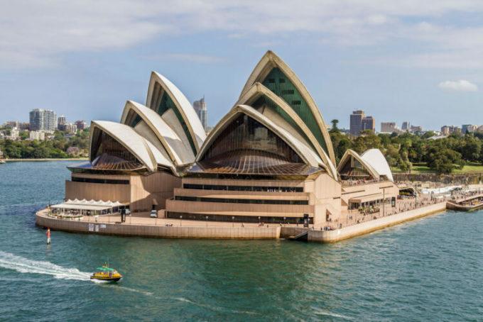 Kiến trúc sư Jorn Utzon nảy ra ý tưởng xây dựng khi ông nhìn thấy một nhóm tàu buồm có vị trí đẹp mắt ở cảng Sydney. Hơn một triệu viên gạch men lấp lánh phủ trên những mái nhà hình cánh buồm hai bên. Bên trong, do các vấn đề về âm thanh, trần nhà đã được bổ sung. Ảnh: KC Hunter/Alamy