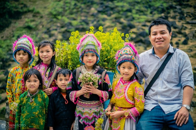 Anh Quý chụp ảnh lưu niệm cùng các bạn nhỏ bán hoa rừng cho du khách ở dốc Thẩm Mã.