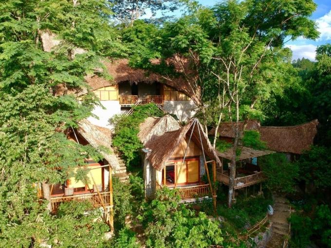 Những căn nhà mái lá cọ ẩn hiện dưới tán cây xanh trong khu nghỉ Moc Chau Retreat. Ảnh: Booking