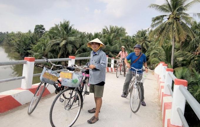 Duy Thịnh (đội nón lá) dẫn khách đạp xe thăm thú xứ dừa miền Tây. Ảnh: NVCC
