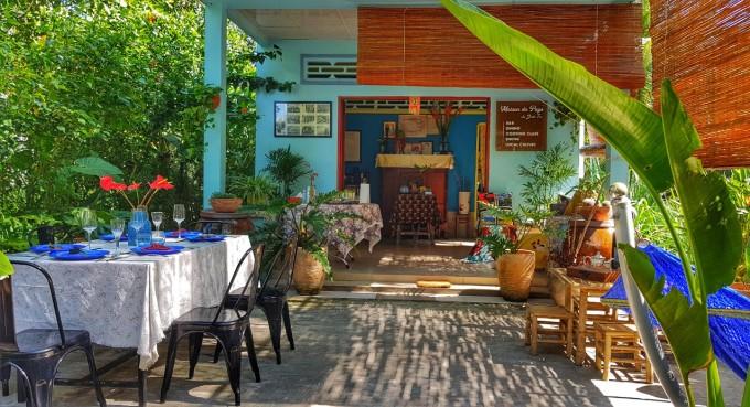 Trước sân nhà anh Thịnh bố trí một bàn ăn nhỏ cho 6 người, kế bên là chiếc võng và bộ bàn tre để uống trà, xung quanh nhà rợp bóng cây xanh. Ảnh: NVCC