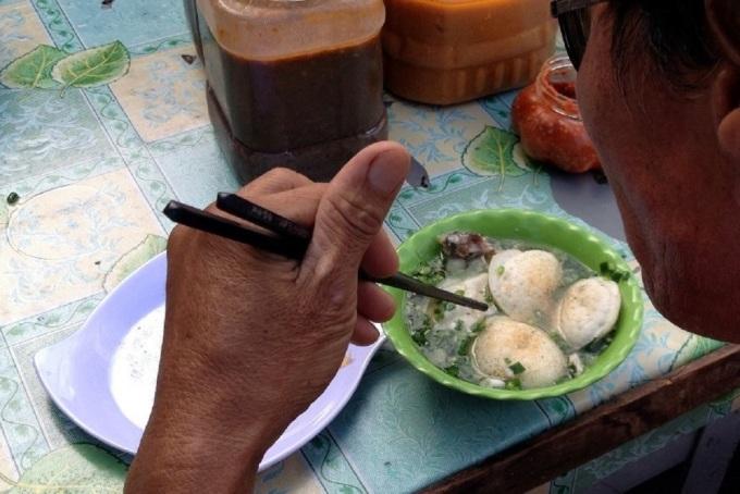 Thưởng thức bánh căn Phan Rang cùng nước cá biển nấu nhạt. Ảnh: Lê Bích